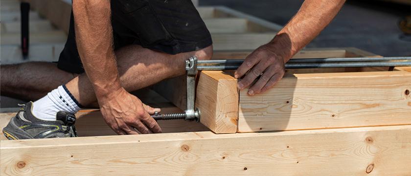 Zimmereiarbeit im Holzbau mit Schraubzwinge