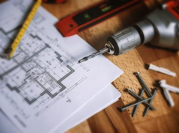 Baupläne und Werkzeug auf Holztisch