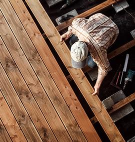 Zimmerer montiert Bretter an Holzterrasse